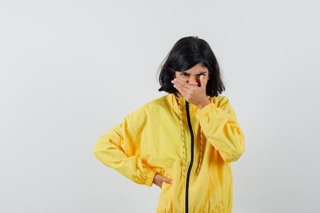 Bambina in felpa con cappuccio gialla tenendo la mano sulla bocca e guardando triste, vista frontale.