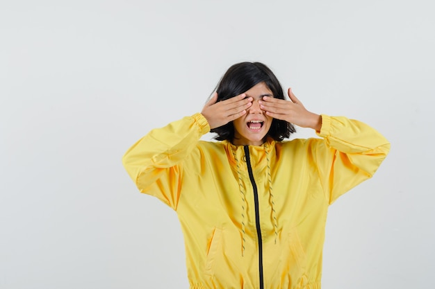 Bambina in felpa con cappuccio gialla tenendo le mani sugli occhi e guardando eccitato, vista frontale.