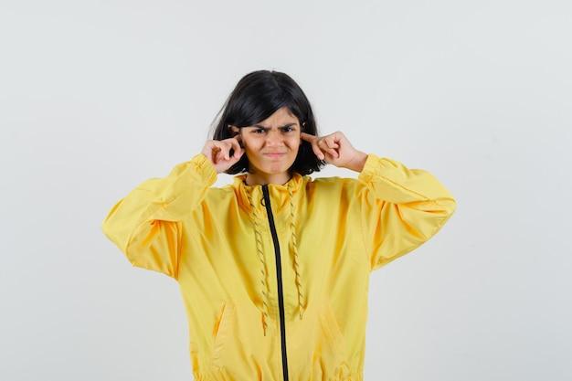 Bambina in felpa con cappuccio gialla tappando le orecchie con le dita e guardando irritato, vista frontale.