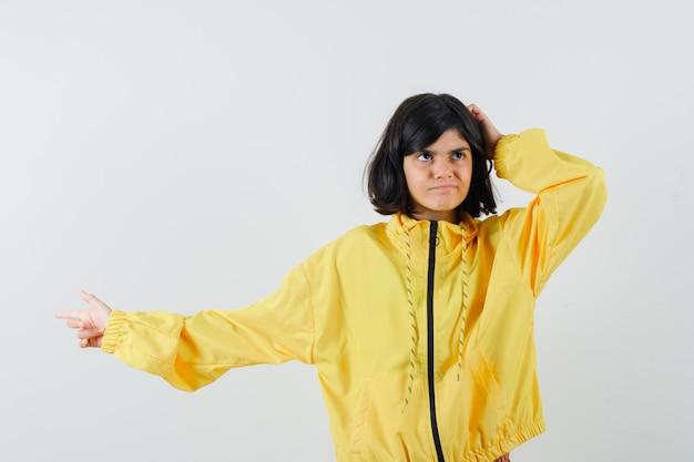 Bambina in felpa con cappuccio gialla che indica da parte mentre si gratta la testa e sembra smemorato, vista frontale.