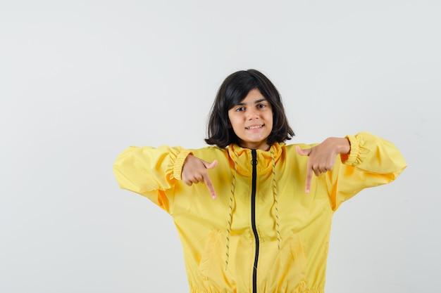 Bambina in felpa con cappuccio gialla rivolta verso il basso e guardando fiducioso, vista frontale.
