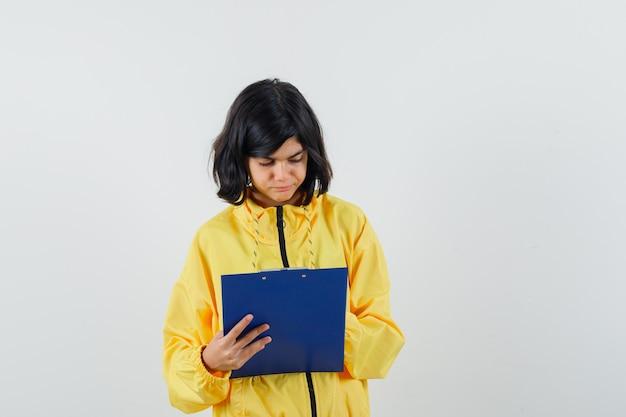 Bambina in felpa con cappuccio gialla che prende appunti negli appunti e sembra occupata, vista frontale.