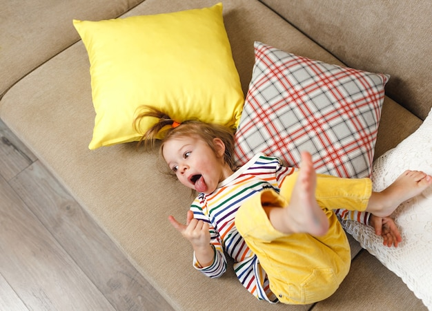 A little girl in yellow pants and a colorful t-shirt lies on her back on the couch and shows her tongue, making fun of it. children's home games. yellow pillows.