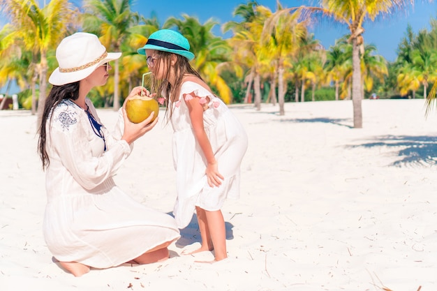 Little girl and young mother with coconut milk on exotic beach