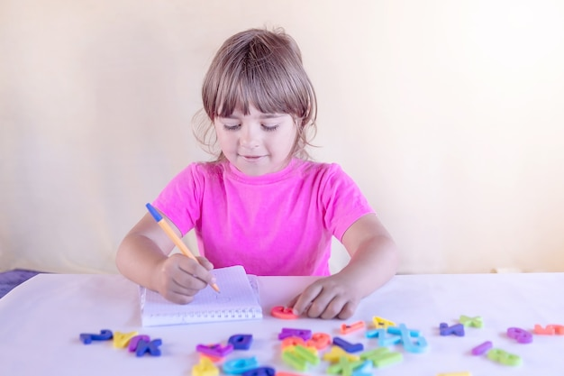 A little girlchild sits at a table with a notebook and letters and smiles