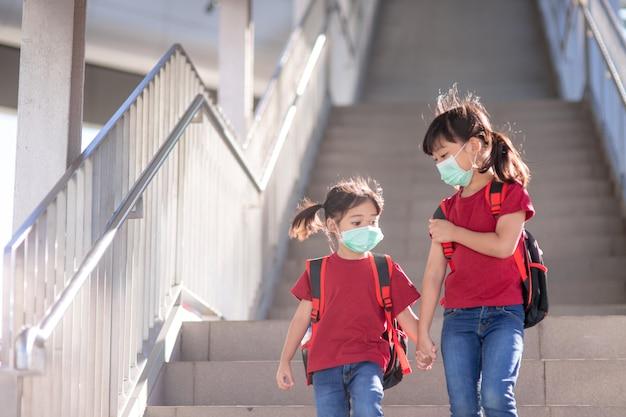 学校のバックパックと保護マスクの小さな女の子と姉妹。ランドセルを運んでいる小学生のビュー。
