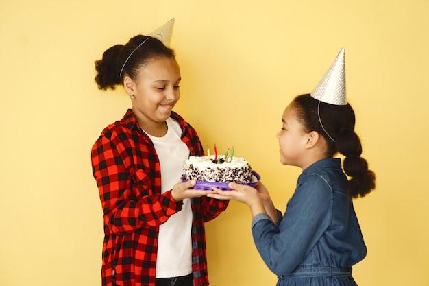 小さな女の子の誕生日は黄色の壁に分離されました。ケーキを持っている子供たち。