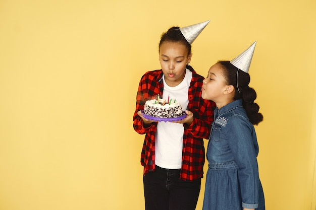 Little girls birthday isolated on yellow wall. children holding cake.