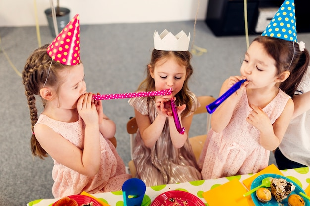 Little girls blowing toys
