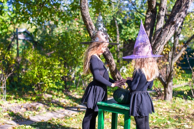 Little girls casting a spell on halloween in witch costume