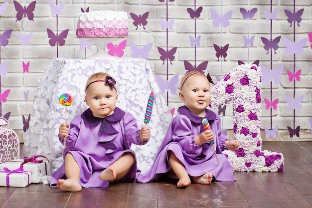 Маленькие девочки празднуют свой первый день рождения