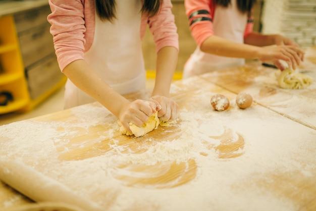Маленькие девочки повара мят тесто, веселые пекари