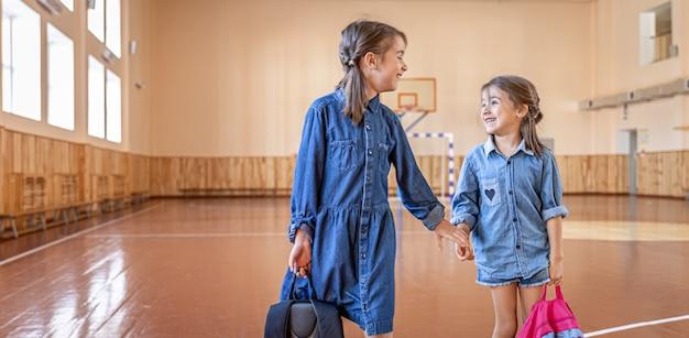 学校の体育館で放課後のバックパックを持った小さな女の子のクラスメート
