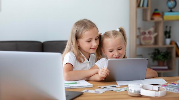 집에서 함께 온라인 학교를 하는 어린 소녀들