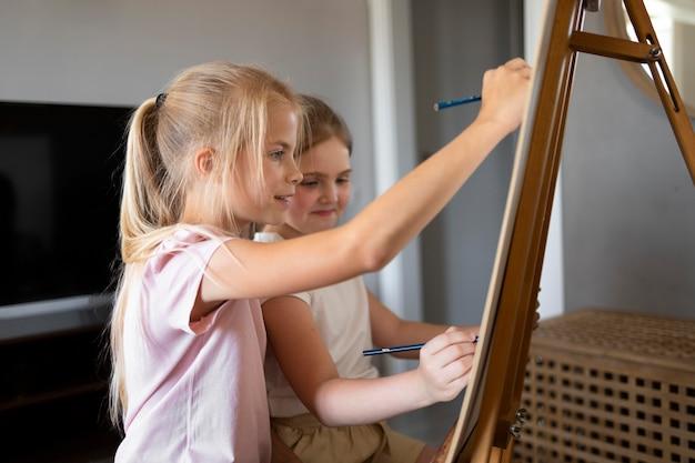 家でイーゼルを使って一緒に描く小さな女の子