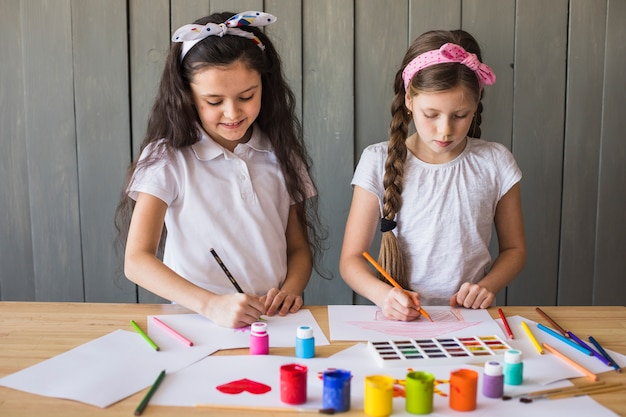 Little girls drawing with colored pencils on white paper over the wooden desk