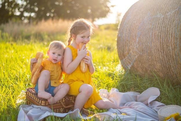 Маленькие девочки едят свежий багет и фрукты на пикнике на закате на природе