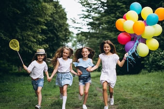 Little girls friends with balloons in forest