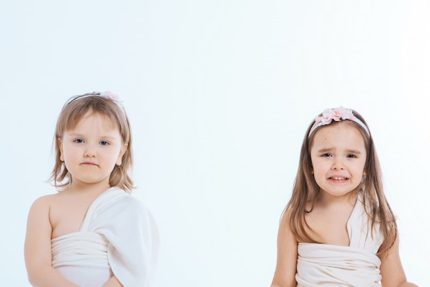 A little girls grimaces against a white background. the children is up to something. concept of emotions , facial expressions, childhood, sincerity
