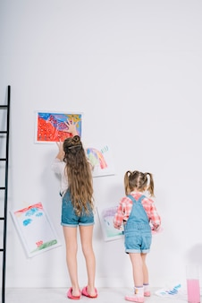 Little girls hanging drawings on white wall