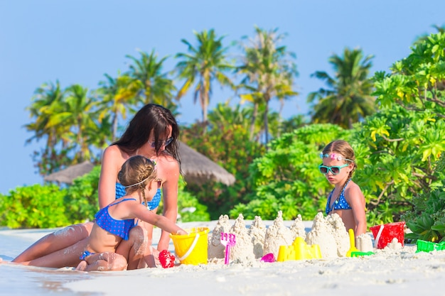 Little girls and happy mother playing with beach toys on summer vacation