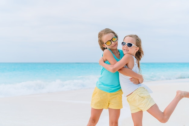 Маленькие девочки веселятся на тропическом пляже во время летних каникул, играя вместе