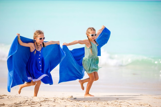 Little girls having fun enjoying vacation on tropical beach