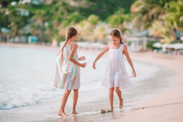 Little girls having fun enjoying vacation on tropical beach