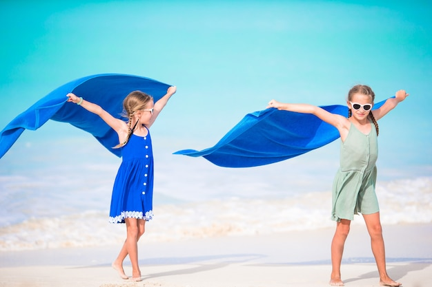 Little girls having fun running with towel and enjoying vacation on tropical beach