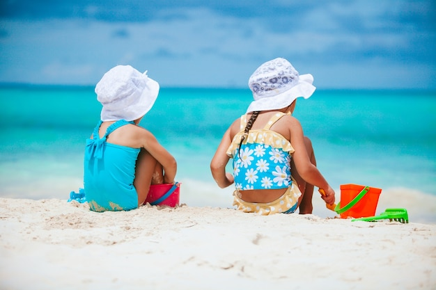 Little girls having fun at tropical beach playing together and making sandcastle