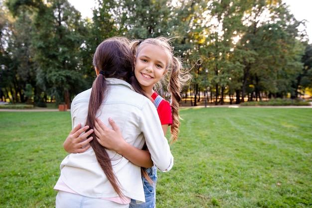 Little girls hugging in the park