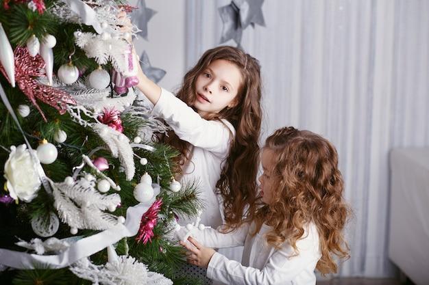 美しいクリスマスの装飾で快適な家庭服を着た小さな女の子
