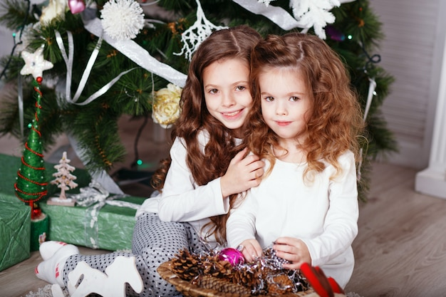 美しいクリスマスの装飾で床に座って快適な家庭服の女の子