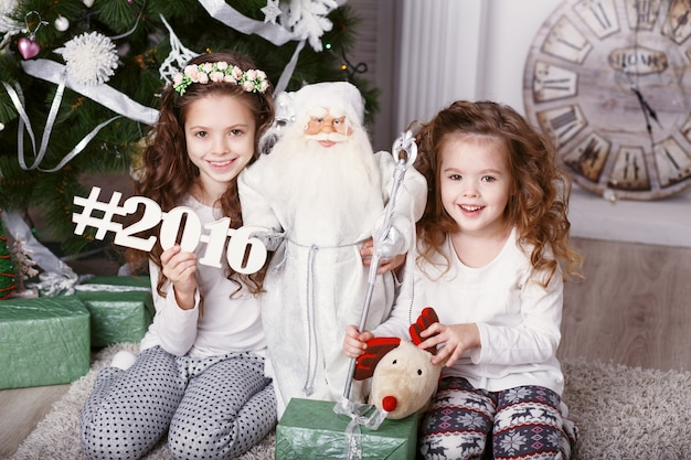 美しいクリスマスの装飾で床に座って快適な家庭服を着た小さな女の子。