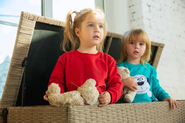 家で遊んでいる柔らかく暖かいパジャマを着た小さな女の子。一緒に楽しんでいるカラフルな服を着た白人の子供たち。