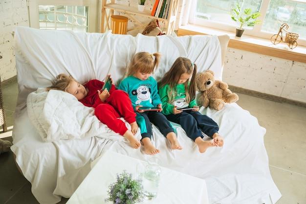 Маленькие девочки в мягкой теплой пижаме играют дома