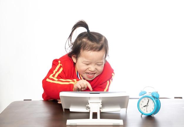 어린 소녀는 태블릿 컴퓨터로 온라인 수업을 배웁니다