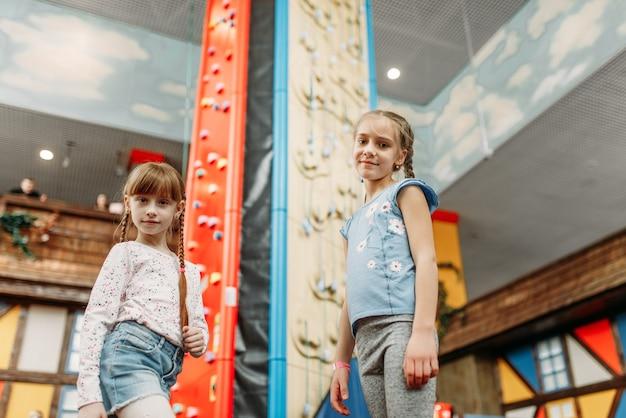 Маленькие девочки смотрят на стену для скалолазания, игровой центр