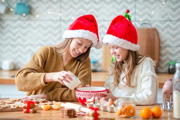 장식 된 거실에 벽난로에서 크리스마스 진저 하우스를 만드는 어린 소녀.
