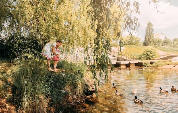 강둑에 있는 어린 소녀들은 오리에게 먹이를 줍니다.