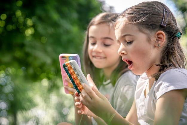にきびのあるケースに携帯電話を持っている屋外の小さな女の子がそれをポップします、流行の抗ストレスおもちゃ。