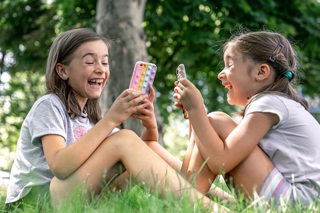 Маленькие девочки на природе с телефонами в чехле от прыщей высовывают модную антистресс-игрушку.