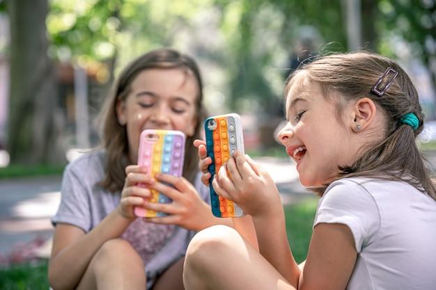 야외에서 어린 소녀들이 여드름이 있는 케이스에 휴대전화를 들고 있는데, 이것은 최신 유행의 스트레스 방지 장난감입니다.