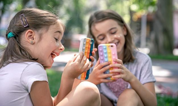 Маленькие девочки на природе с телефонами в футляре от прыщей - это модная антистрессовая игрушка.