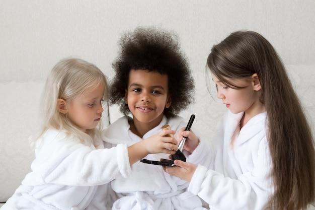 Маленькие девочки играют с косметикой, сидя на диване.