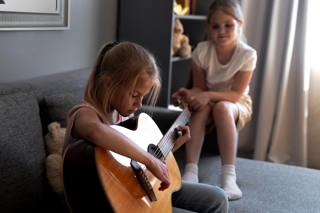 Little girls playing acoustic guitar together at home