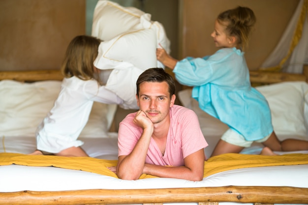 Little girls playing at home on bed near their father