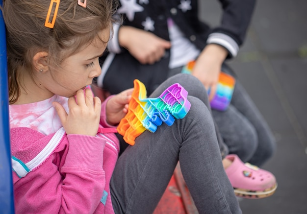 Little girls playing a new fidget toy popular with children helps them to concentrate.