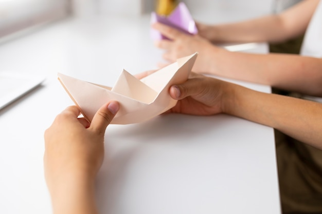Little girls playing with origami paper at home