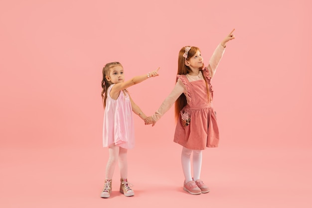 Little girls pointing on pink wall